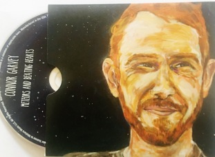 Interior of Meteors & Beating Hearts album jacket, showing stylized watercolor of Connor Garvey against starry background, with CD half-protruding from its sleeve.