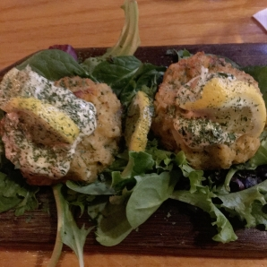 Two splendid crab cakes on a bed of greens.