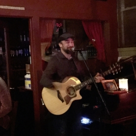 Shawn Taylor playing acoustic guitar in dark wine bar.